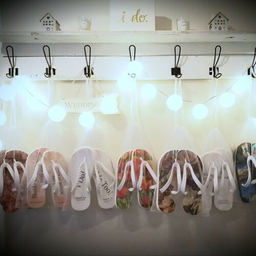 flip flops hanging from hooks, with lights above them.