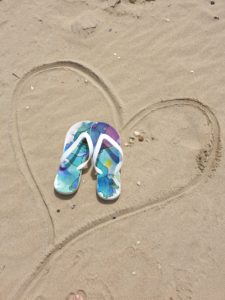 Flip Flops in the sand with a heart shape surrounding them
