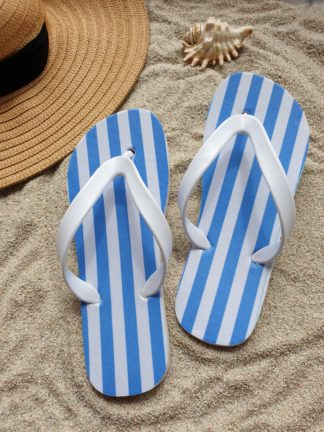 Blue striped Flip Flops in the sand with a hat and a shell