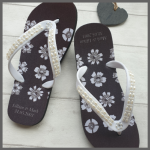 Black flip flops with white flowers
