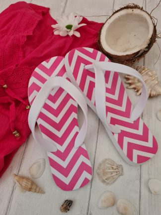 Pink zig zag Flip Flops next to shells and a coconut