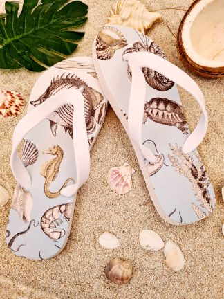 Pale blue Flip Flops with images of sea life on them in the sand
