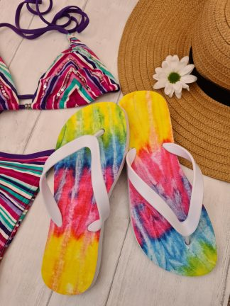 A pair of tie die Flip Flops next to a bikini and sunhat