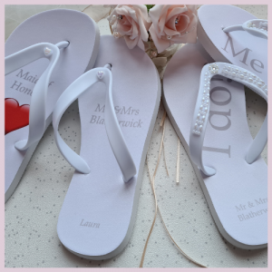 Two pairs of wedding Flip Flops with some flowers
